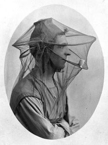 L0011629 Postcard: mosquito net to be worn as a veil.